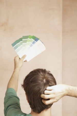 arms behind head: Man Comparing Paint Color Samples