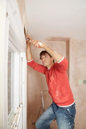 scraping: Man preparing wall of unrenovated room