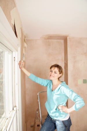 scraping: Woman standing in unrenovated room with scraping tool in hand