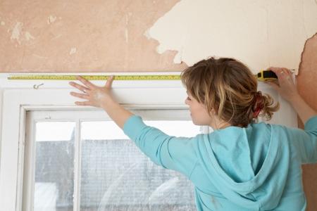 casual hooded top: Mujer que mide marco de la ventana interior Vista posterior LANG_EVOIMAGES