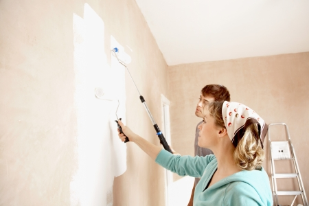 painting: Couple painting wall with paint rollers indoors LANG_EVOIMAGES
