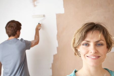 Woman smiling while man roller paints interior wall Stock Photo - 19075625