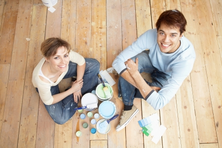 Couple sitting on floorboards amongst paint pots view from above Stock Photo - 19213715
