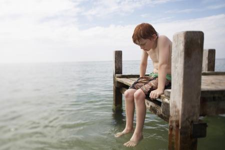 preteen boy: Pr�-adolescent gar�on assis � l'extr�mit� d'une jet�e avec les pieds dans l'eau portrait