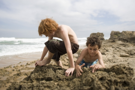 preteen boys: Two pre-teen boys playing in sand on beach LANG_EVOIMAGES