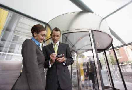 two people with others: Businessman showing businesswoman PDA in front of revolving door low-angle view LANG_EVOIMAGES