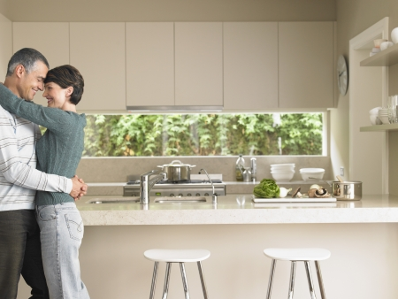 early 40s: Affectionate Married Couple in Kitchen