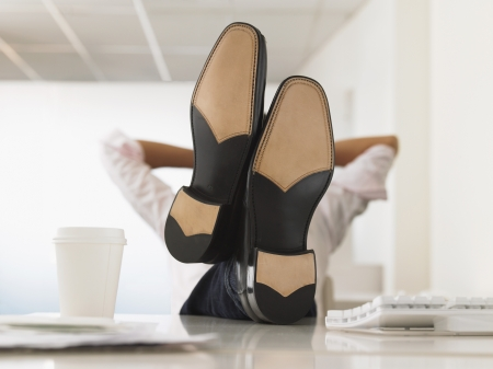 bad manners: Businessman with Feet Up on Desk obscured face LANG_EVOIMAGES