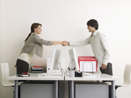 Man and Woman Shaking Hands over Desks side view Stock Photo - 19075675