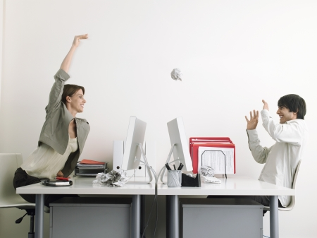 battle of the sexes: Woman throwing paper at man in office side view