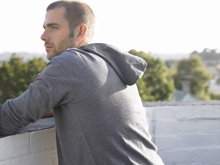 casual hooded top: Hombre que mira sobre balc�n de longitud media