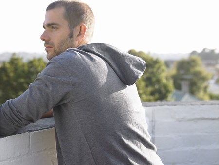 casual hooded top: Man looking over balcony half length