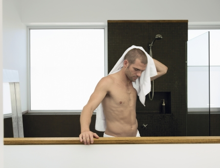 partially nude: Man drying himself in bathroom