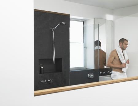 Man leunt tegen gootsteen in de badkamer