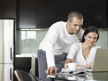 lap top: Couple looking at lap top in modern kitchen