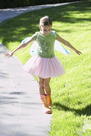 fairy wings: Girl wearing fairy wings and tutu balancing on edge of path portrait