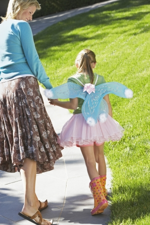 fairy wings: Girl wearing fairy wings and tutu walking with mother on park path back view