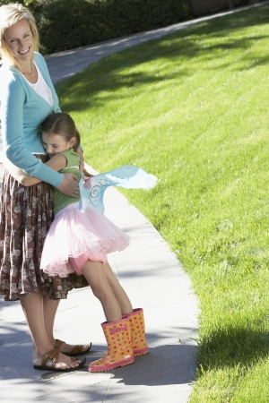 fairy wings: Girl wearing fairy wings and tutu hugging mother in park