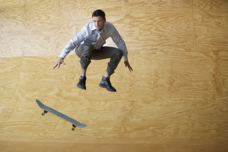 capable: Young Businessman Performing Skate Trick in Half-Pipe