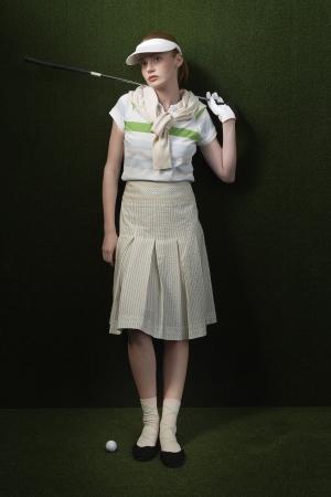 visor: Woman in visor holding golf club behind shoulders portrait