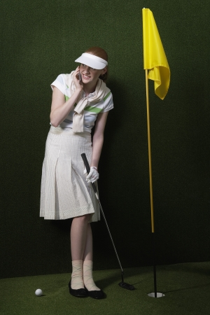 visor: Woman in visor holding golf club by flag in hole