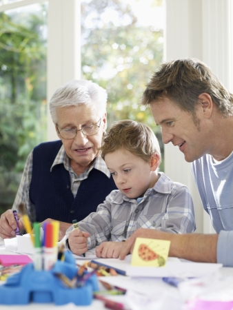 multi generational: Boy (3-4) drawing with crayons with father and grandfather in house