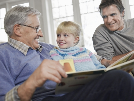 multi generational: Grandfather reading to girl (3-4) father looking on in house