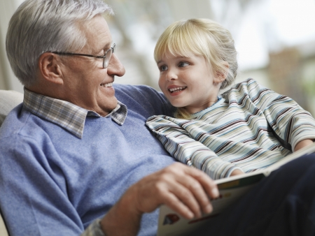 Grandfather reading to girl (3-4) close-up Stock Photo