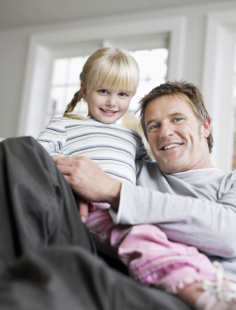Girl (3-4) sitting in father's lap in house portrait low angle view Stock Photo - 19213593