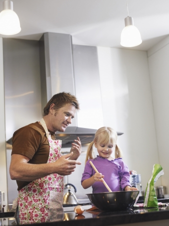 reversal: Girl (3-4) and father baking in kitchen