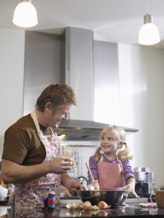 role reversal: Girl (3-4) and father baking in kitchen