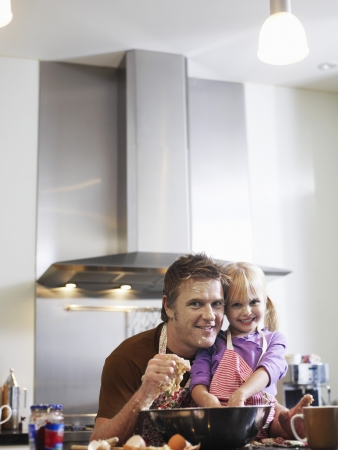 ��role reversal�: Girl (3-4) and father baking in kitchen portrait