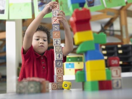 edificio escuela: Ni�o de escuela primaria jugando con bloques de construcci�n