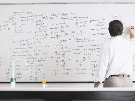Teacher Writing on Whiteboard Stock Photo