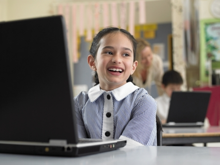 grinning: School Girl Using a Laptop