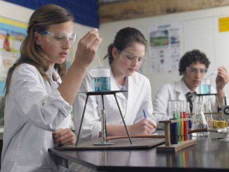 bata de laboratorio: Los estudiantes de secundaria que estudian en el laboratorio