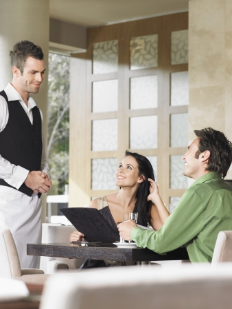 opting: Couple in Restaurant Choosing from Menu