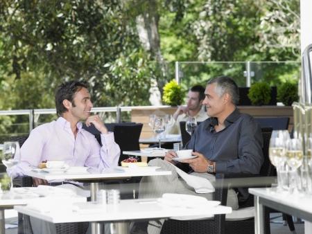 two men talking: Two men talking at outdoor cafe LANG_EVOIMAGES