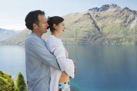 Couple embracing looking at mountain lake