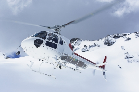 rescue helicopter: Helicopter flying over snowy mountain peaks LANG_EVOIMAGES