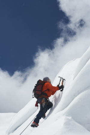 mountain climber: Alpinista salendo pendio nevoso con gli assi LANG_EVOIMAGES