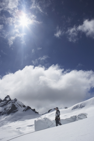 mountain climber: Alpinista in piedi sul pendio nevoso LANG_EVOIMAGES