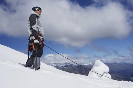 mountain climber: Alpinista in piedi sul pendio nevoso con linea di sicurezza allegata LANG_EVOIMAGES