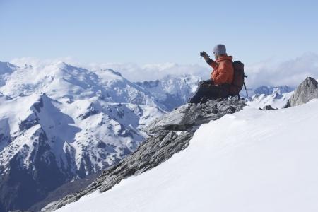mountain climber: Alpinista di scattare una foto sulla cima di una montagna