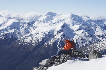 mountain climber: Alpinista con laptop sul picco di montagna