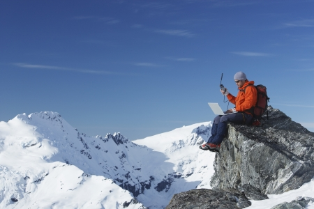 Mountaineer Using Laptop and Satellite Phone LANG_EVOIMAGES