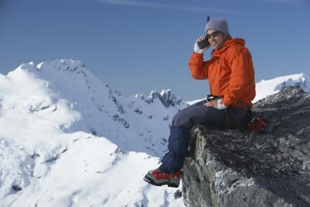 mountain climber: Alpinista con walkie-talkie su picco di montagna LANG_EVOIMAGES