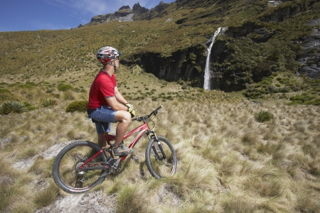 mountainbiking: Mountainbiker Looking at Waterfall