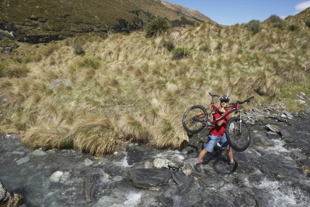 mountainbiking: Mountainbiker Carrying Bike Through Stream LANG_EVOIMAGES