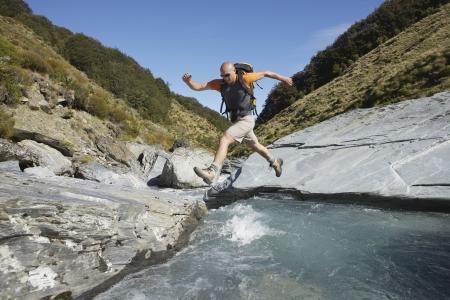nimble: Hiker Jumping Over Mountain River